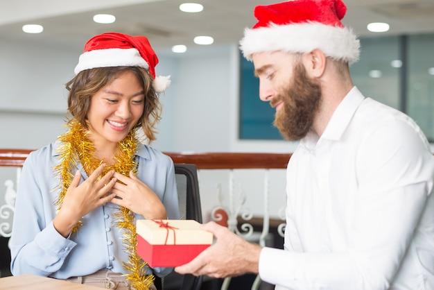 Líder da empresa positiva dando presentes de natal Foto gratuita