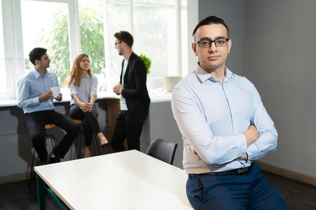 Líder de negócios bonito confiante posando na sala de reuniões Foto gratuita