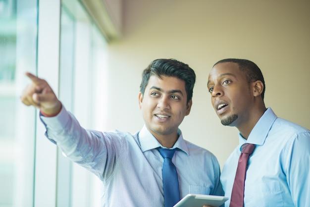 Líder de negócios jovem mostrando o prédio vizinho ao investidor Foto gratuita