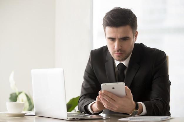 Líder empresarial masculino navegando recursos on-line usando gadgets Foto gratuita