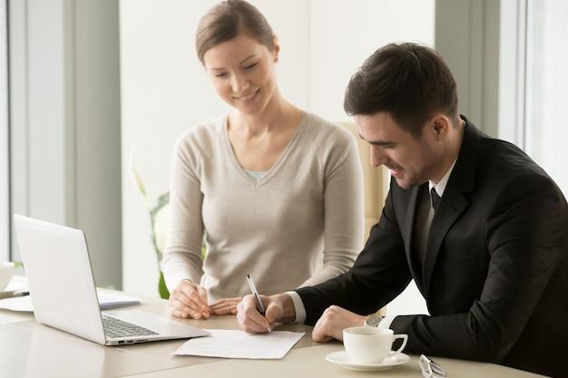 Líderes empresariais feminino e masculino, assinando contrato Foto gratuita
