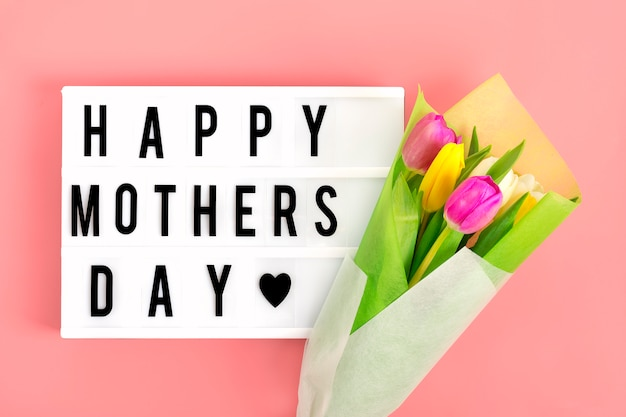 Lightbox com citação dia das mães feliz, tulipas coloridas sobre fundo rosa. Foto Premium