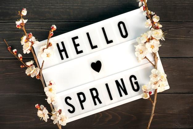 Lightbox com citação olá primavera e raminhos da árvore de alperce com flores Foto Premium