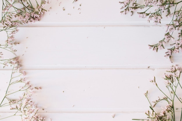 Lilac pequenas flores sobre uma mesa de madeira com espaço no meio Foto gratuita