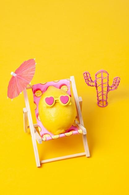 Limão em óculos de sol no solário com guarda-chuva na praia Foto Premium