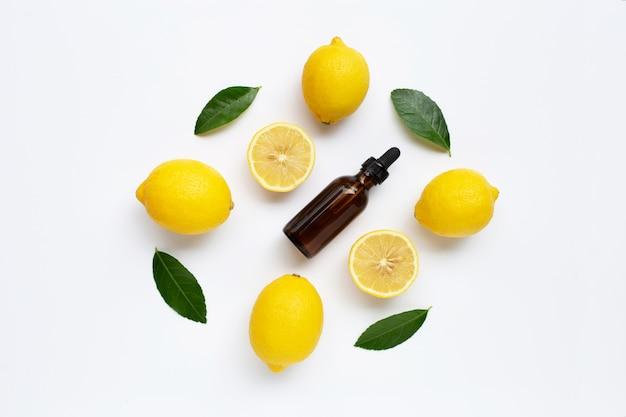 Limão fresco com óleo essencial de limão no fundo branco. Foto Premium