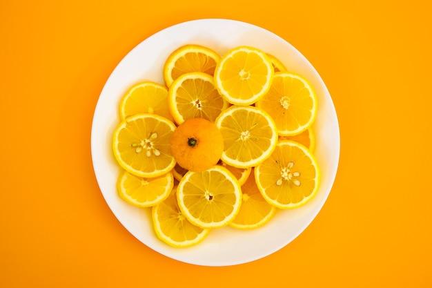 Limões amarelos em um prato em um dia ensolarado Foto gratuita