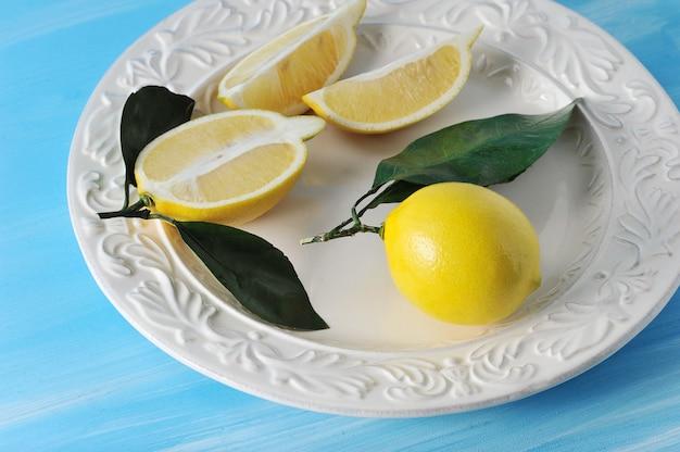 Limões amarelos frescos com folhas em um prato sobre fundo azul de madeira Foto Premium