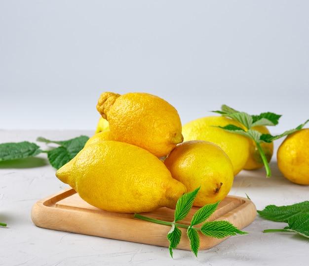 Limões amarelos inteiros maduros frescos, ingredientes para fazer bebidas de verão Foto Premium