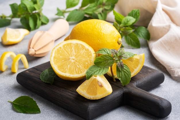 Limões amarelos suculentos inteiros e cortados com folhas de hortelã fresca Foto Premium