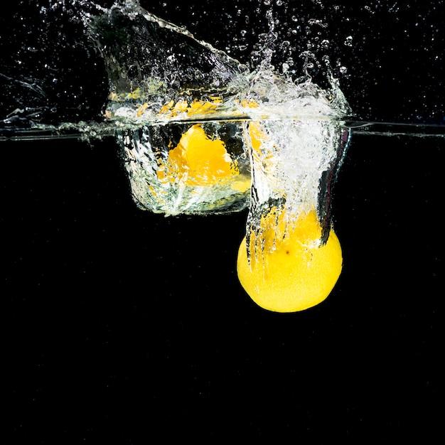 Limões caindo em respingos de água Foto gratuita