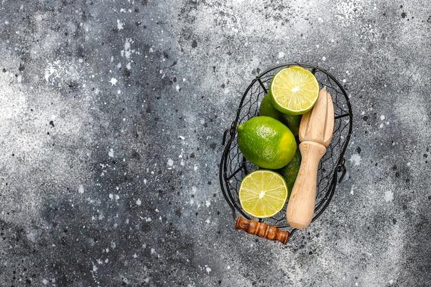 Limões-chave frescos com espremedor de citrinos de madeira, vista superior Foto gratuita