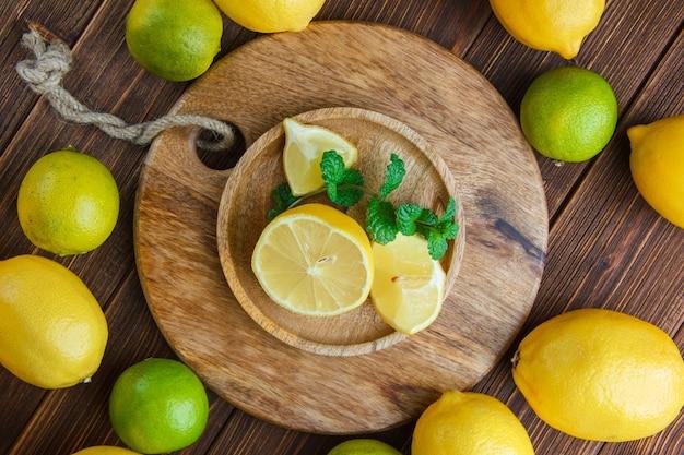 Limões com limas, folhas em uma placa de madeira na tábua de madeira e corte, plana leigos. Foto gratuita