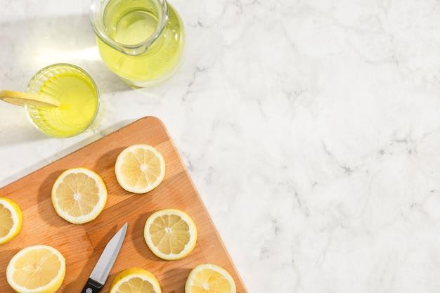 Limões cortados na vista superior da placa de madeira Foto gratuita