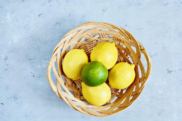 Limões e cais frescos em uma cesta em um fundo azul. citrino. Foto Premium