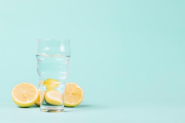 Limões e vidro no fundo azul Foto gratuita