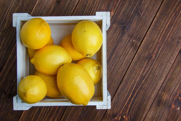 Limões em uma caixa de madeira plana colocar em uma mesa de madeira Foto gratuita