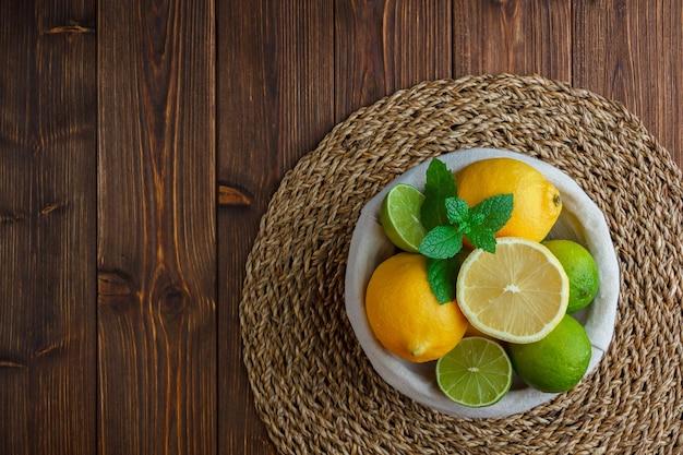 Limões em uma cesta sobre uma superfície de madeira. vista do topo. Foto gratuita