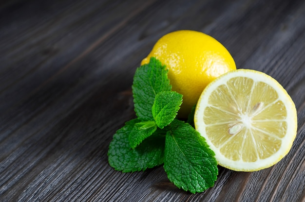 Limões frescos e folhas de hortelã na mesa de madeira escura. Foto Premium