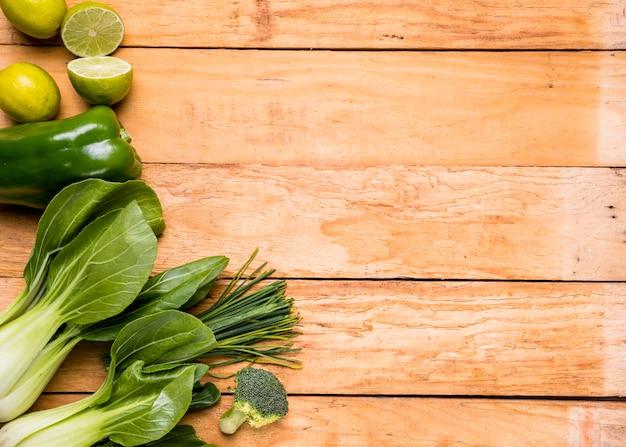 Limões; pimentões; brócolis; cebolinha e bokchoy na prancha de madeira Foto gratuita