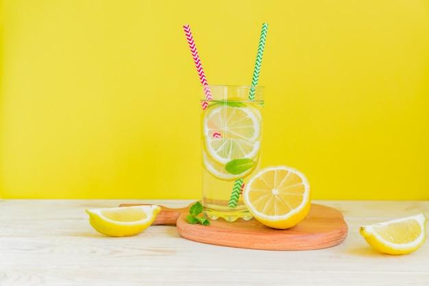 Limonada caseira com limão e hortelã sobre fundo amarelo colorido. bebida gelada de verão cocktail. copyspace Foto Premium