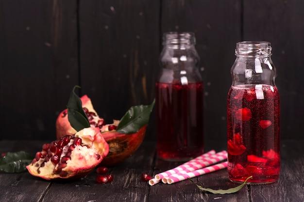 Limonada caseira de romã vermelha em pequenas garrafas de vidro Foto Premium