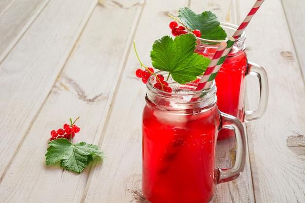 Limonada caseiro da passa de corinto vermelha em um frasco de pedreiro com a decoração da baga na tabela de madeira do ligth. Foto Premium