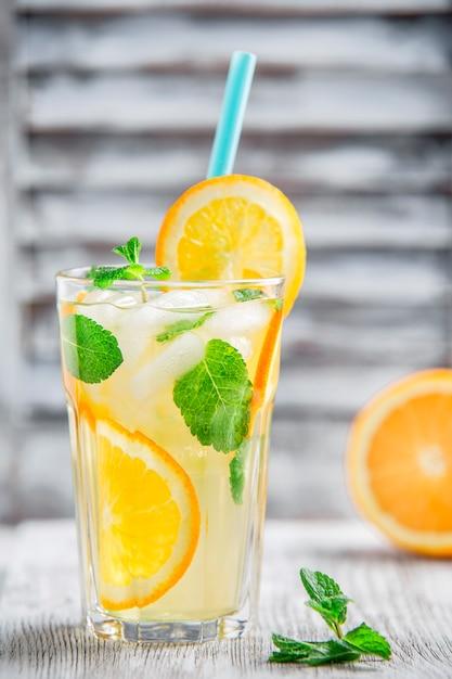 Limonada com laranja e gelo no fundo da janela de faixa branca Foto Premium