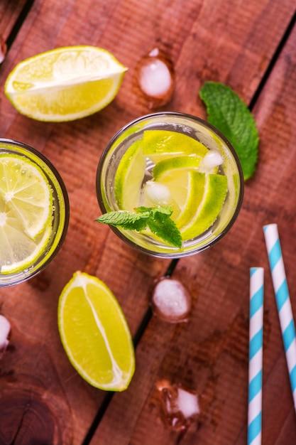 Limonada com limão fresco e hortelã no fundo de madeira Foto Premium