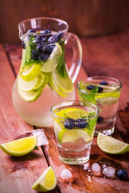 Limonada com limão fresco, frutas e hortelã no fundo de madeira Foto Premium