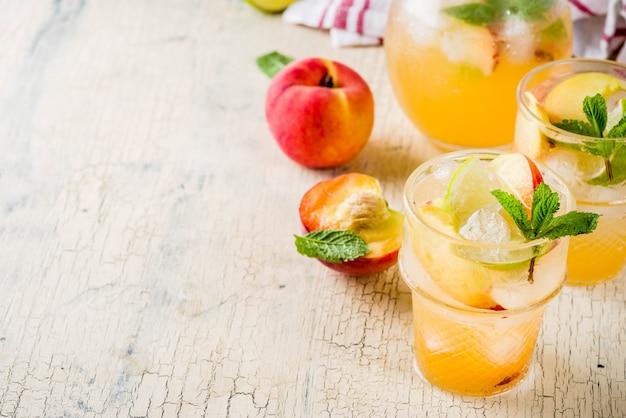 Limonada de pêssego e limão, mojito cocktail com enfeite de frutas frescas Foto Premium