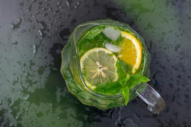 Limonada de refrescamento do verão em um vidro transparente, hortelã, estragão, limão. tonificado Foto Premium