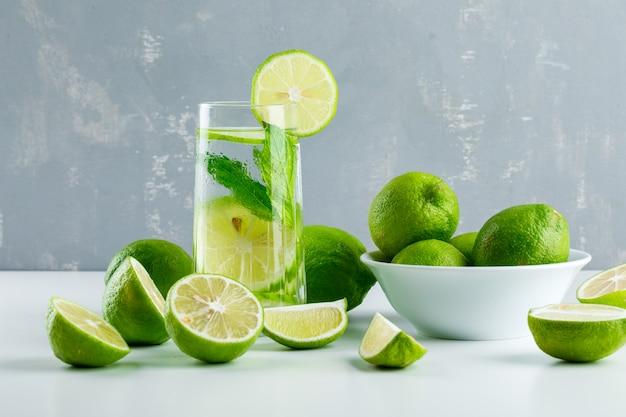 Limonada em um copo com limões, ervas vista lateral em branco e gesso Foto gratuita