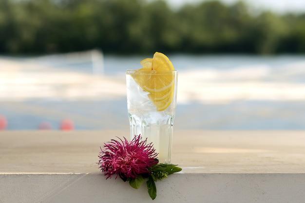 Limonada transparente com gelo e limão em uma taça de vidro. com decoração de flores Foto Premium
