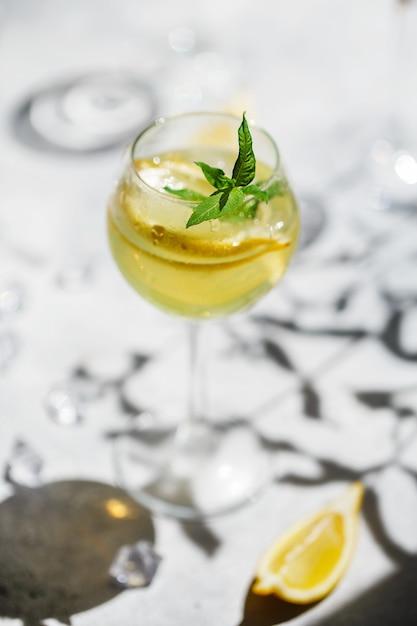 Limoncello caseiro em um copo sobre uma perna fina. um cocktail margarita com uma rodela de limão no copo. Foto Premium