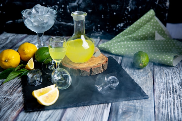 Limoncello digestivo típico italiano com limões frescos na fumaça, foco seletivo Foto Premium