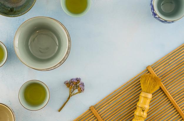 Limonium flor com xícaras vazias e escova no pano de fundo texturizado branco Foto gratuita