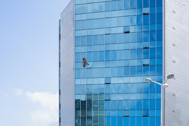 Limpador de janelas trabalhando em uma fachada de vidro suspensa Foto Premium