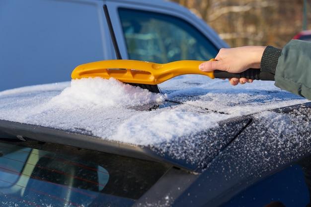 Limpando a neve do teto de um carro com uma escova Foto Premium