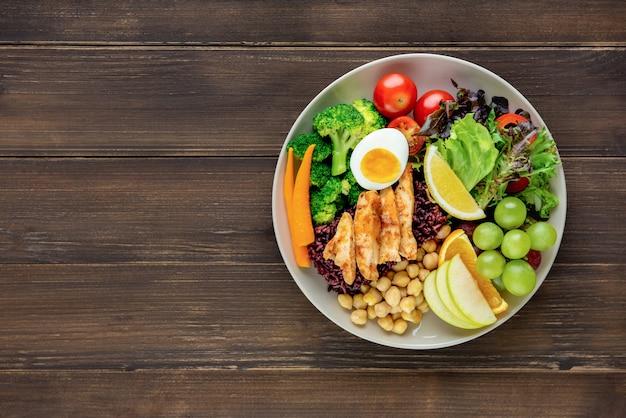 Limpar alimentos com vegetais mistos e salada de frutas no fundo da mesa de madeira Foto Premium