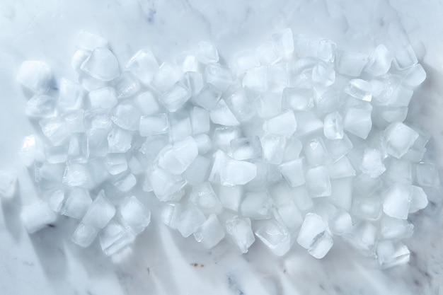 Limpe cubos de gelo frio em um fundo de mármore cinza Foto Premium