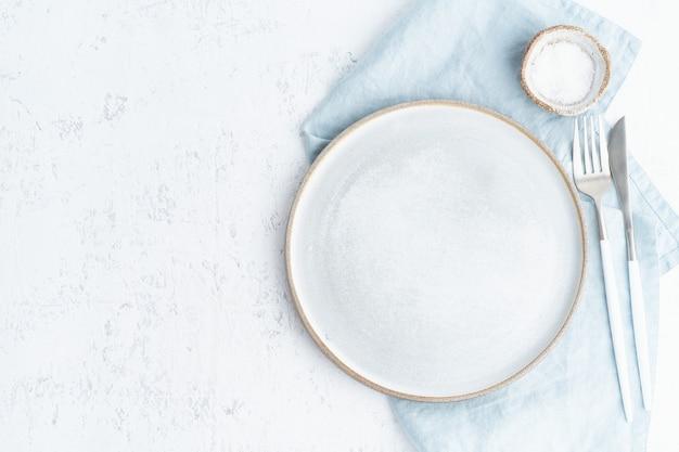 Limpe o prato de cerâmico branco vazio, garfo e faca na mesa de pedra branca, copie o espaço, mock-se Foto Premium