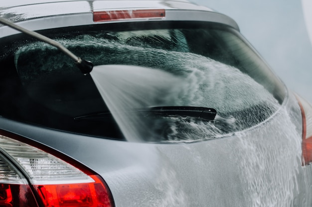 Limpeza de carro usando água de alta pressão. Foto Premium
