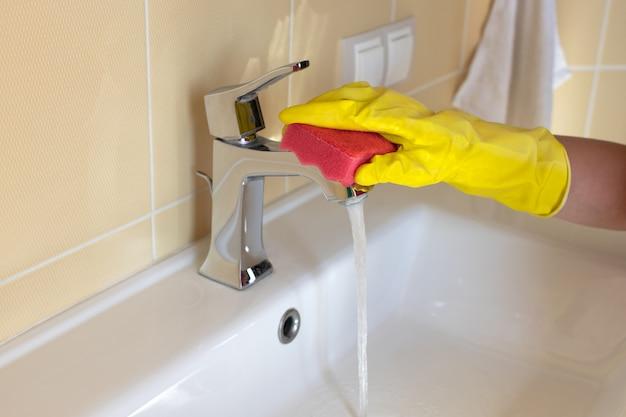 Limpeza de pia e torneira de banheiro com detergente em luvas de borracha amarela e esponja rosa. Foto Premium