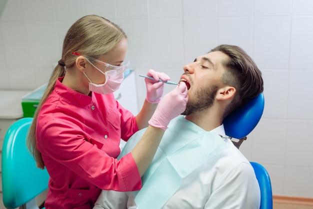 Limpeza profissional dos dentes, o dentista limpa os dentes de um paciente do sexo masculino. Foto Premium