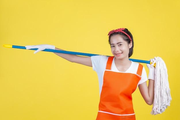 Limpeza. uma mulher bonita com um dispositivo de limpeza em um amarelo. Foto gratuita