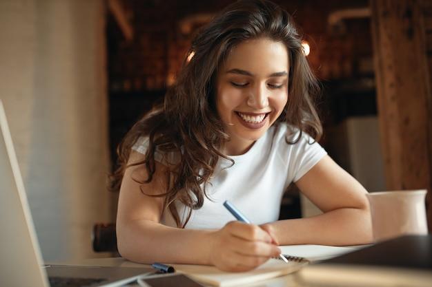 Linda aluna com bochechas rechonchudas segurando uma caneta escrita à mão no caderno enquanto aprende à distância de casa Foto gratuita