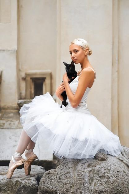 Linda bailarina acariciando gato preto Foto gratuita