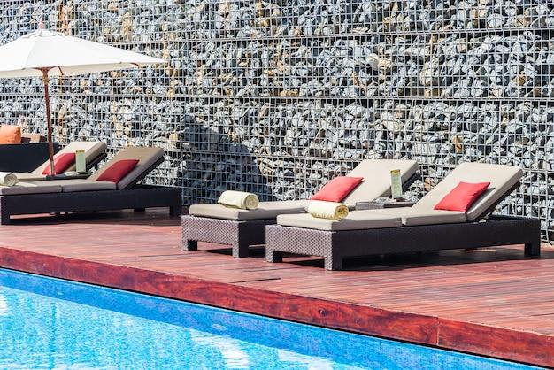 Linda cadeira de luxo com deck de guarda-chuva e piscina resort Foto gratuita