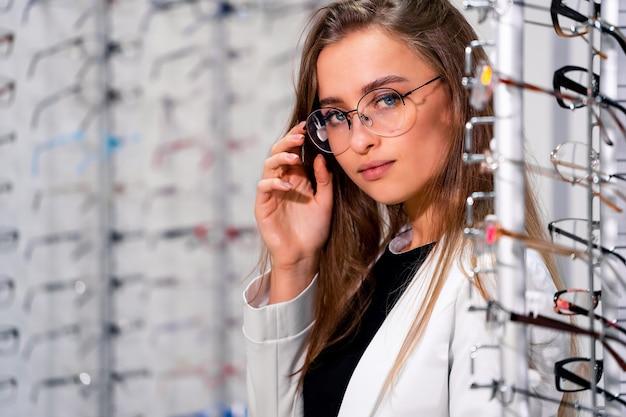 Linda cliente ou oculista está de pé com poucos óculos na loja de ótica Foto Premium